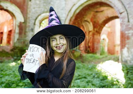 Friendly halloween witch in black hat and attire asking for a treat