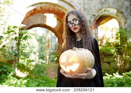 Little girl in black warlock and eyeglasses holding halloween pumpkin