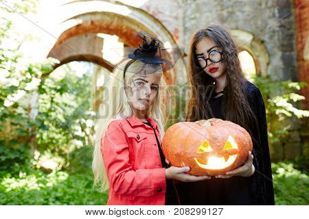 Little friends in halloween attire sharing jack-o-lantern at carnival party
