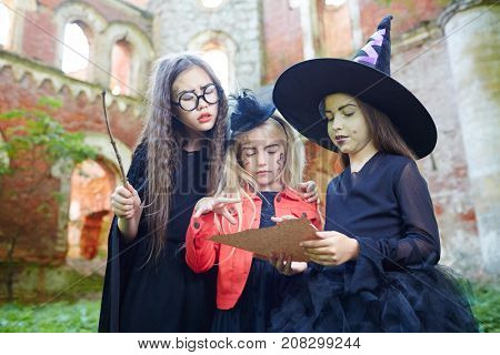 Little girls in witch attire reading halloween spell on paper