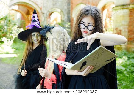 Halloween girl with open spell book doing witchcraft with her friends on background