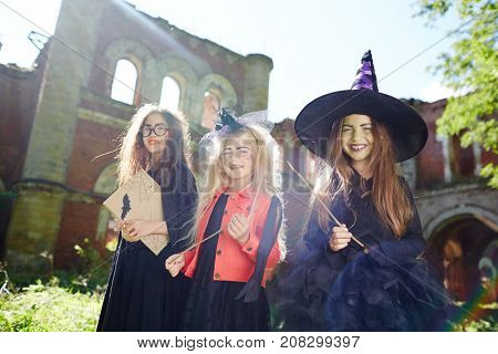 Girls in halloween costumes holding magic-sticks and book of spells