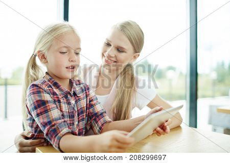 Cute girl with tablet discussing curious online video with her mother
