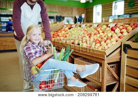 Happy girl sitting in shopping cart while her father pushing it while choosing food products in supermarket