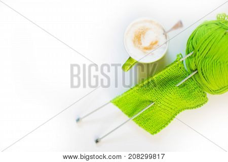 Knitted Knitted Green. Yarn For Knitting Green. White Background. Coffee Cappuccino.