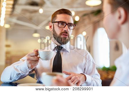 Businessman with cup of tea consulting his subordinate during coffee-break