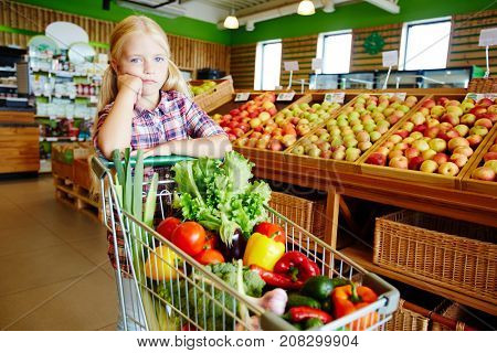 Adorable buyer pushing shopping cart in modern hypermarket in vegetable department