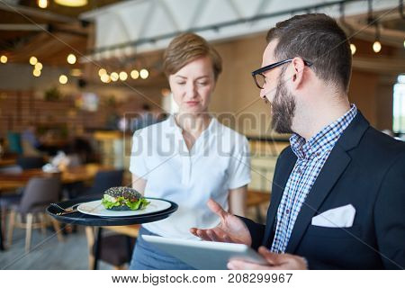 Waitress with tray bringing to businessman with tablet ordered sandwich for lunch