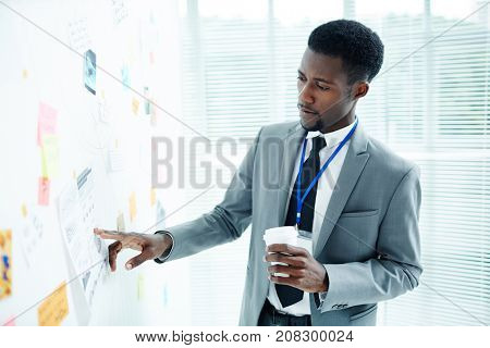 Portrait of concentrated African American FBI agent holding paper cup of coffee in hand while thinking over committed crime, he standing at marker board with collected evidence