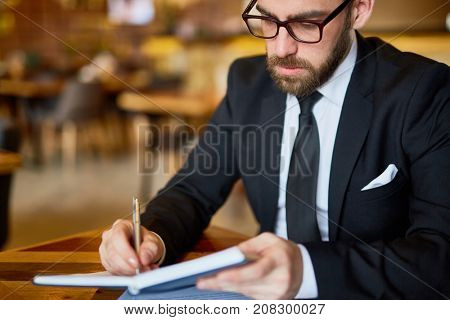 Confident business expert or employer making notes in notebook