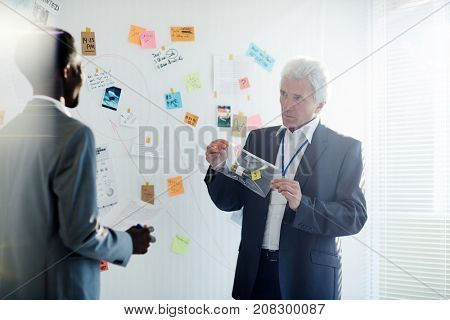 Highly professional mature detective holding evidence from crime scene in hands while presenting his point of view concerning possible murder suspects, his Afro-American colleague listening to him