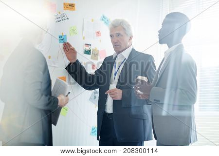 Mature FBI agent sharing ideas concerning possible suspects with colleagues while conducting working meeting at open plan office, they using investigation board