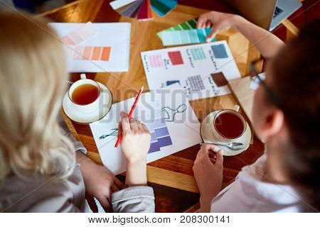 Contemporary fashion designers having discussion of fabric samples and color swatches
