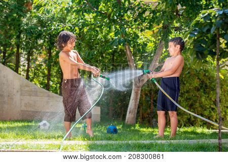 Two siblings playing with water