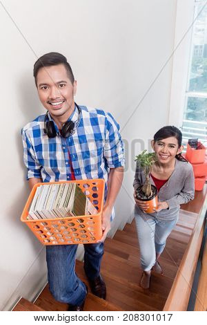 Young asian couple, woman and man, carrying their stuff to new apartment during relocation