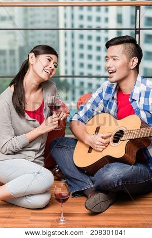 After moving together in city apartment young man plays love song for his girlfriend on guitar