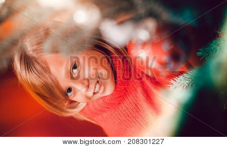 Young girl helping decorating the Christmas tree, holding some Christmas baubles in her hand