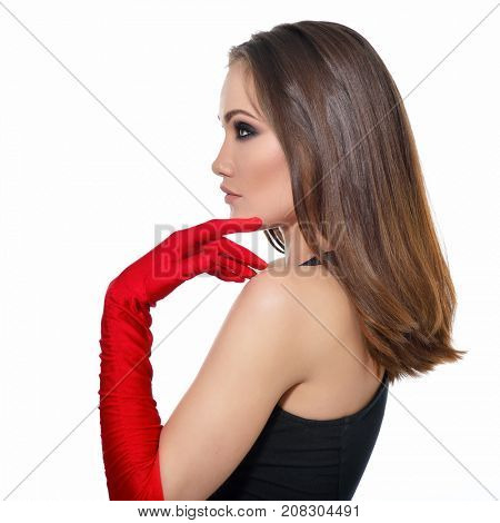 Fashionable woman. Beautiful female face in profile. Woman of high society. Heartbreaker. Beauty woman. Portrait of amazing young fashion woman posing at studio in red gloves and black dress