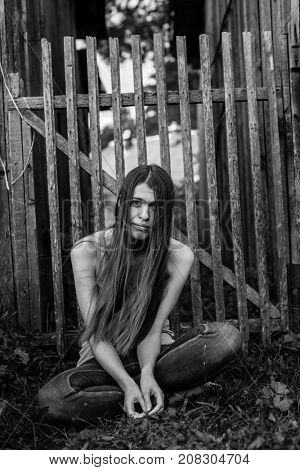 Young woman with long hair in jeans sitting near the wooden fence. Black-and-white photo.