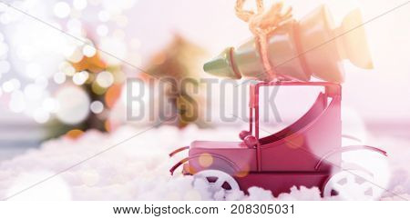 Toy car carrying christmas tree on fake snow during christmas time