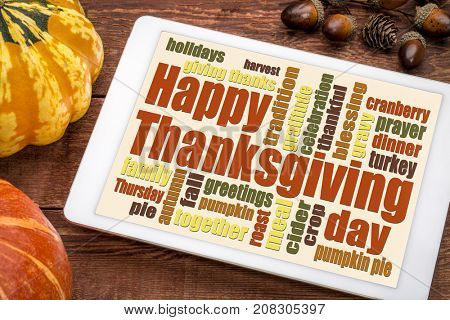 Happy Thanksgiving word cloud on a digital tablet with pumpkin and acorn decoration