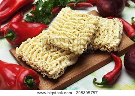 Raw asian instant noodles on wooden board with vegetables