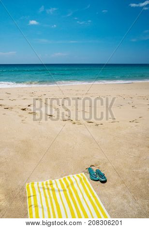 Beautiful sandy beach with towel and flip flops over blue sea and sky background