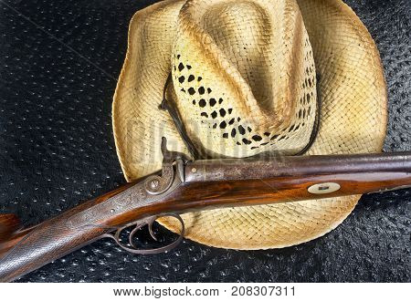 Antique double barrel shotgun and straw hat.