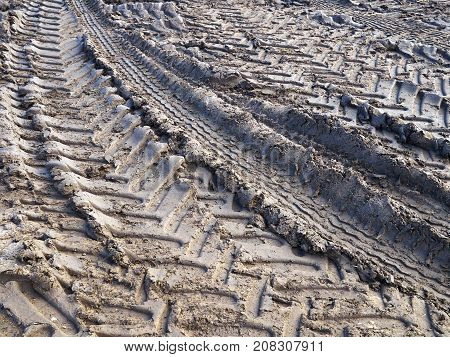 Track of tractor tires wheels on mud ground soil agriculture background image