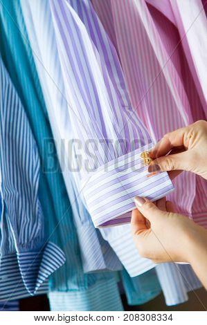 A Woman Picks Up A Man Cufflinks For The Shirt. Choosing Cufflinks.