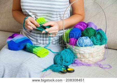 A woman in a gray dress knit socks from colored yarn. Balls of colored yarn are in the basket.