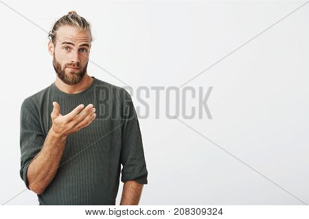 portrait of handsome swedish man with trendy hairdo and beard in casual grey clothes looking in camera with surprised expression and gesticulating with hand