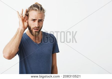 Good-looking swedish guy with beard and cool hairstyle holding hand near ear showing he don't hear last words that his friend says