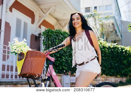 Smiling woman rent a bike,summer, laughing girl, flowers in the basket