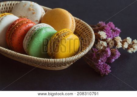 Colorful French macaron or Italian macaron stack on basket. Homemade delicious macaron on granite table with copy space for background or wallpaper. French dessert for served with tea or coffee. Pastel color macaron on granite table.