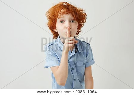 Portrait of little ginger boy with curly hair and freckles holding finger near lips, showing his friend to don't speak loudly