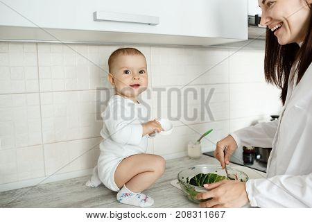 Portrait of cheerful little baby boy sitting on kitchen table, smiling and trying to help mother with cooking salad while mom brightfully smiling