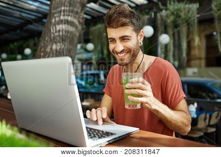 Positive Caucasian bearded man with earphones on sitting in front of generic laptop computer working outdoors, holding glass of lemonade. Working freelancer sitting at cafe with open notebook pc on wooden table.