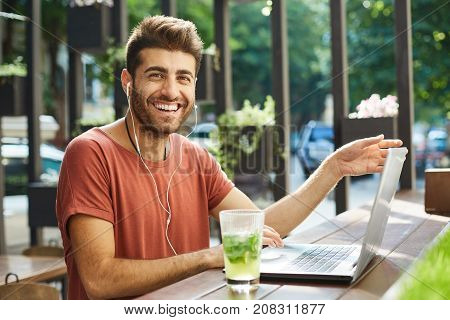 Smiling to the camera bearded man with dark hair and beard, casually dressed, typing on keyboard of generic laptop, working on promotional text outdoors. Freelancer wearing earphones enjoying lunch break, drinking lemonade on a summer day.