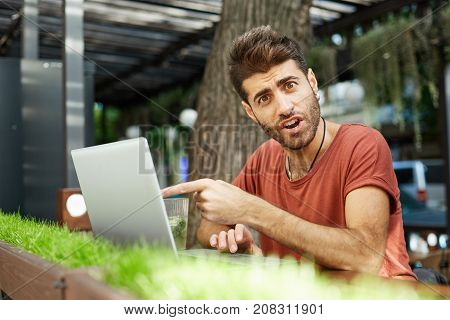 Good-looking young man with beard in red t-shirt having puzzled and surprised expression after recieving message, looking at the camera with misunderstandment and open mouth, pointing at the screen of his laptop. Suddenness concept.
