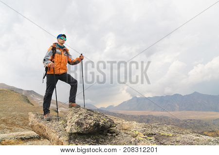A lonely tourist with a backpack and wearing sunglasses enjoys the views high in the mountains of the Caucasus where there is no grass, the village and snow at sunset.