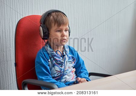leisure, education, children, technology and people concept - boy with computer and headphones at office.