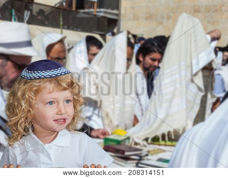 Autumn Jewish holiday Sukkot. Lovely blonde boy with blue eyes in a skullcap. People in white Taliths pray at the Western Wall of the Temple