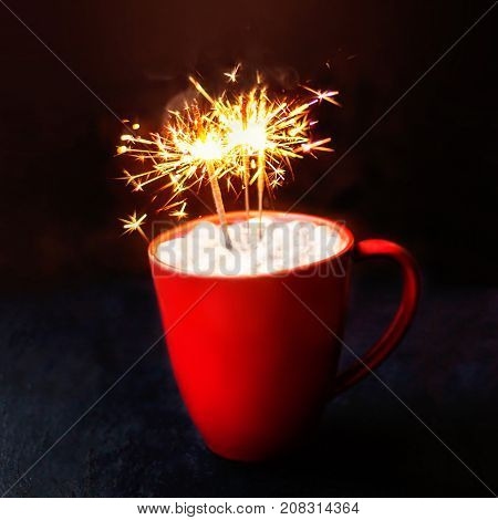 Christmas Card with hot chocolate in a red mug sparkling bengal fireworks lights on dark background