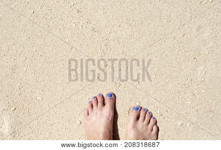 Woman feet on white sand beach. Relaxed barefoot woman by sea. Seaside banner template with text place. Summer vacation poster background. Bare feet of girl on coral beach. Sunny sand beach texture