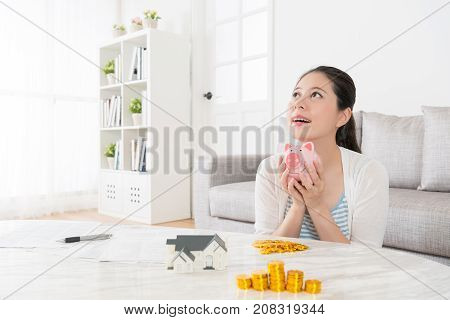 Slim Housewife Saving Money Into Piggy Bank