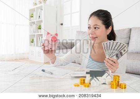 Smiling Happy Female Model Holding Pink Piggy Bank