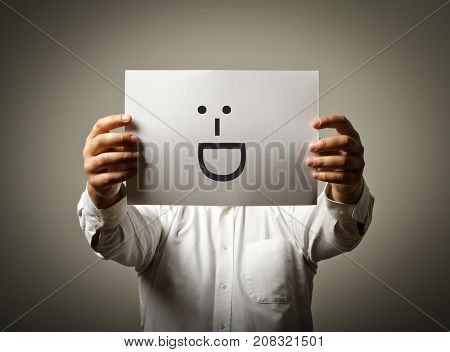Man is holding white paper with smile. Laughing and smiling concept.