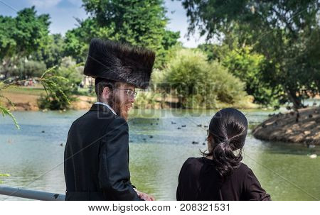 RAMAT-GAN ISRAEL - OCTOBER 6 2017: Orthodox jewish man and girl looking on pond in municipal park. Israel