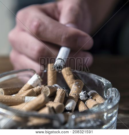 hand of man smoking cigarette with ashtray full of cig butt end and ash in disgusting unhealthy addiction and bad habit calling for quitting tobacco addiction and keep healthy lifestyle